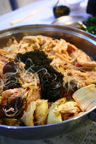 A metal dish holds several cooked ingredients including 髮菜 (fà cài/black moss), 粉絲 (fěn sī/glass noodles), beancurd skin, and leafy vegetables.  The black moss is clumped together in the middle of the dish.  Little or no sauce is visible.