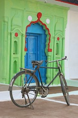 Pretty door and bike, Orchha, India (greenwood100) Tags: door travel blue red india white black green art beautiful smart bike bicycle festival handle stand asia paint pretty arch bright bell lakshmi painted spoke spokes wheels transport vivid gear clean chain doorway cycle frame atlas diwali peddle hindu hinduism saddle handlebars tyre bold mudflap orcha madhyapradesh orchha crossbar urchha paintedbuildingsinindia