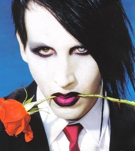 Marilyn Manson holing a rose in mouth