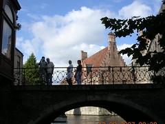 Bridge over tranquil waters. (davidezartz) Tags: travel bridge blue trees windows roof light shadow sky people plants brown white house black green water glass leaves sunshine stone architecture clouds reflections grey boat canal still nikon europe arch photographer belgium belgique bricks brugge smooth bridges peaceful calm canals loveit tiles waters bruges serene picturesque flemish railings tranquil magicmoments chimneys placid veniceofthenorth e3100 unruffled nikone3100 forf nikonstunninggallery mywinners abigfave worldbest top20travel ysplix naturephotoshp top20bridges fiveflickrfavs alongbrugescanals bridgeovertranquilwaters wonrerfulworldmix