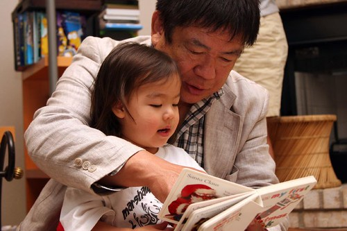 photo showing a man reading to a little girl