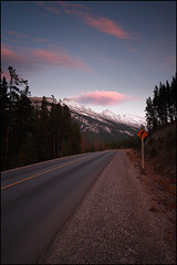 Lonely planet (itspaulkelly) Tags: road travel pink sunset sky canada mountains travelling sign clouds highway alberta banff banffnationalpark