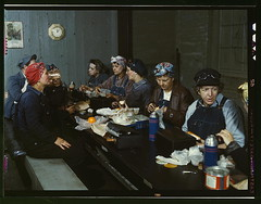Women workers employed as wipers in the roundhouse having lunch in their rest room, C. & N.W. R.R., Clinton, Iowa  (LOC) (The Library of Congress) Tags: railroad food orange history clock fruit lunch workers women calendar eating candid rosie wwii working goggles drinking iowa 1940s overalls jar americans denim conversation libraryofcongress noon lunchbox patriots bandana railways cantina bottleopener thermos 1943 lunchbreak womensday 1207 clintoncounty dirtyhands dorag redfingernails historicalphoto jackdelano xmlns:dc=httppurlorgdcelements11 dc:identifier=httphdllocgovlocpnpfsac1a34808 marcellahart elibiasiematter