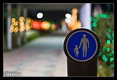 Take care of your kid (Khalid AlHaqqan) Tags: street sign night canon 350d 50mm lights parents bokeh walk figure kuwait f18 khalid ahmadi aplus outstandingshots abigfave kuwson platinumphoto alhaqqan diamondclassphotographer goldstaraward pedisterian