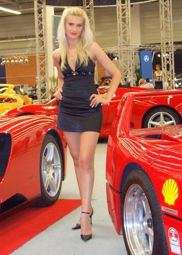 Blonde model in black dress on luxury car show