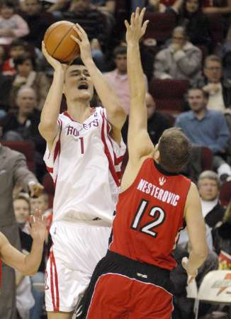 Yao Ming double-pumps in mid-air over Toronto's Rasho Nesterovic before shooting the ball toward the basket, which bounced around the rim for a bucket in the fourth quarter.  Yao led the way in the fourth quarter with 8 big points, and would lead all scorers with 25 points on 8-of-19 shooting, and 9-of-9 from the free throw line, to give Houston a 91-79 victory over the Raptors.