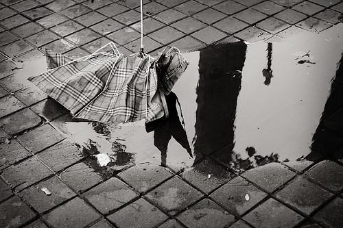 Fotografía en blanco y negro de una acera adoquinada tras un día de lluvia, un charco y un paraguas roto dan testimonio de la tempestad