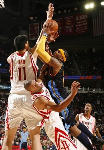 Yao Ming comes over defensively to help Shane Battier defend against Denver's Carmelo Anthony taking it to the hoop Saturday night.  Yao finished with 22 points on 9-of-18 shots, and grabbed 13 boards in a rare 109-81 blowout against a Nugget team that has now shot below 40% for three straight games.