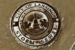 Storm Sewer Cover-Lansing (SCOTTS WORLD) Tags: adventure america art rusty crusty digital decay detail lansing michigan midwest sewer cover sidewalk sign panasonic pov perspective february winter 2017 capitol fun light framed cropped salt outside outdoors