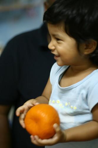 Marielle holding a mandarin orange