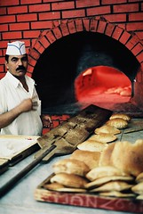 Memories of Hajj 1429 : A Bakery In Makkah (W  M Soo) Tags: food film analog bread analogue nikkor50mmf18 naan mekah makkah fujisuperia200 freshfromtheoven nikonfm kingdomofsaudiarabia flickrdiamond staplefood masjidkuching hajj1429 wmsoo 2biji1rial orangmesir manzoorelectricalbakery rotiarab masrian