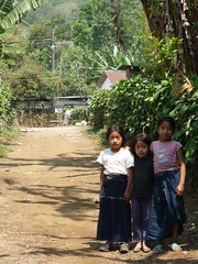 Three girls standing on a road.