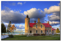 Mackinaw City Light House with Mighty Mac (Craig - S) Tags: city bridge blue windows roof red sky sun lighthouse tree water clouds flag stormy explore beacon mackinacbridge mackinac mackinaw slates mackinawbridge mackinawcity straightsofmackinaw mightymac straightsofmackinac mackinacpointlighthouse