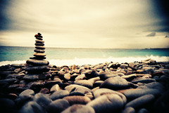 Balanced rocks on the Nice Promenade (Cormac Phelan) Tags: ocean sea france film beach water 35mm nice lomo lca xpro lomography lka velvia vignette phelan cormac rockbalancing