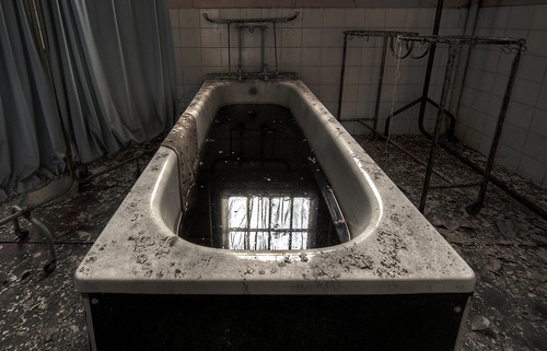 image of a bathtub with black water in it, in an abandoned room