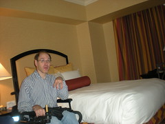 Darrell in his wheelchair, sitting beside the bed