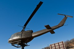 A retired Army helicopter on display at a war memorial just east of Mineral Wells, TX. (colorblindPICASO) Tags: bird outside lightsandshadows flight cockpit bluesky pole elevated warmemorial afternoonsun armygreen bellhelicopter armyhelicopter rotorblade mineralwellstexas