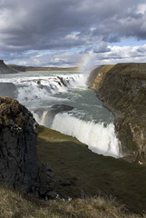 Gullfoss, golden falls, Iceland's iconic waterfall and rainbow (jackie weisberg) Tags: sky cloud mountains water norway vertical clouds landscape island volcano lava waterfall iceland rainbow skies lakes bluesky spray norwegian photograph waterfalls massive rivers glaciers nordic blueskies rainbows elegant volcanic barren geysir gullfoss tundra fjords basalt puffyclouds arcticcircle gulfstream pristine geysers goldencircle goldenfalls silica geothermalpower hydroelectricity sandfields egalitarian ingolfurarnarson glacialrivers economiccrisis temperateclimate volcanicallyactive therepublicoficeland jackieweisberg
