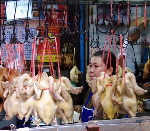 אשה ותרנגולות בשוק האוכל של צ'יינה טאון