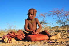 preparing the red pomade (luca.gargano) Tags: africa travel red people colour feet girl stone child african culture tribal safari afrika tribe ethnic exploration namibia tribo himba angola afrique ethnology tribu namibie gargano tribus namibe ethnie ovahimba himbas lucagargano muhimbas muhimba
