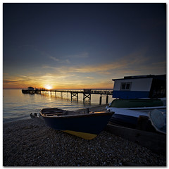 Blue Monday - A fish & chip sunset at Totland Bay (s0ulsurfing) Tags: ocean blue light sunset sea summer sky cloud sun sunlight seascape texture tourism beach nature water weather silhouette june clouds composition square landscape boats island evening bay coast pier vanishingpoint lyrics seaside interesting twilight skies quiet peace sundown natural dusk jetty wide shoreline silhouettes wideangle pebbles calm explore coastal filter shore isleofwight vista coastline ripples grad landschaft isle 2009 squared wight mellow neworder fishchips 10mm converging totland bluemonday sigma1020 nd4 totlandbay s0ulsurfing totlandpier coastuk vertorama
