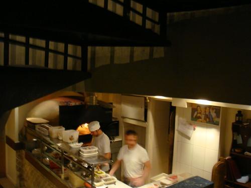 Cocineros en acción con el horno de leña al fondo