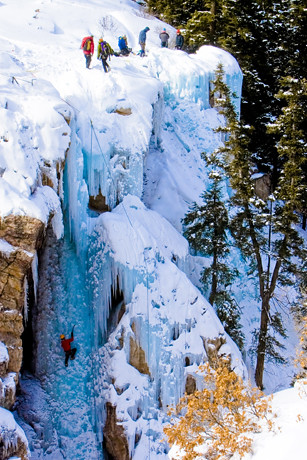 Ice climbers challenging themselves on a frozen waterfall in the Ouray Ice Park by Visit Colorado.