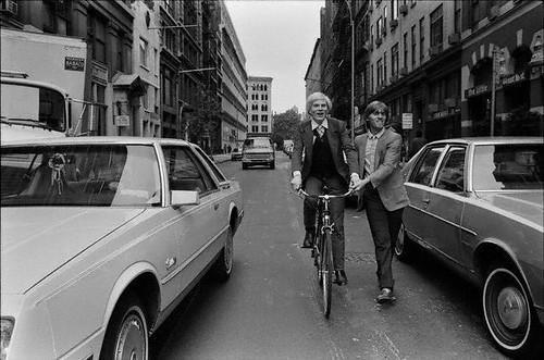Menino, segura aqui senão eu caio! Andy Warhol brincando de pedalar nas ruas de New York
