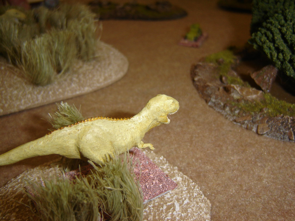Tyrannosaur surges out of high grass towards armoured car