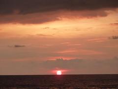 The sun setting over the sea.