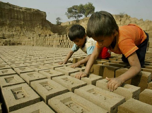 children working stacking bricks