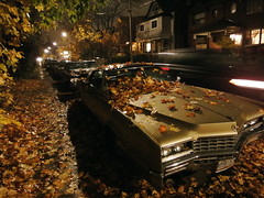 Leafy Cadillac in Autumn #2 (Roger Cullman) Tags: autumn red orange toronto fall wet leaves car rain yellow twilight lowlight streetlight colours windy cadillac autumnleaves oldcar leafy slowshutterspeed bordenstreet wx1 sonywx1 photorogercullmanallrightsreserved