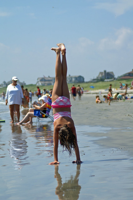 Young woman in bikini performing handstand