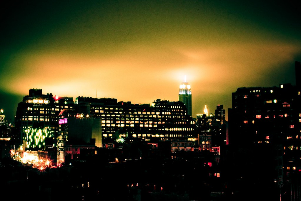 NYC at night lit by the Empire State building and the lights of the meat packing district