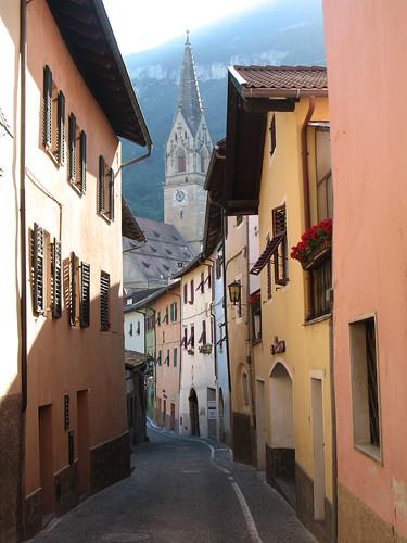Alte Gasse im historischen Dorfkern mit Blick auf die Traminer Kirche im Hintergrund