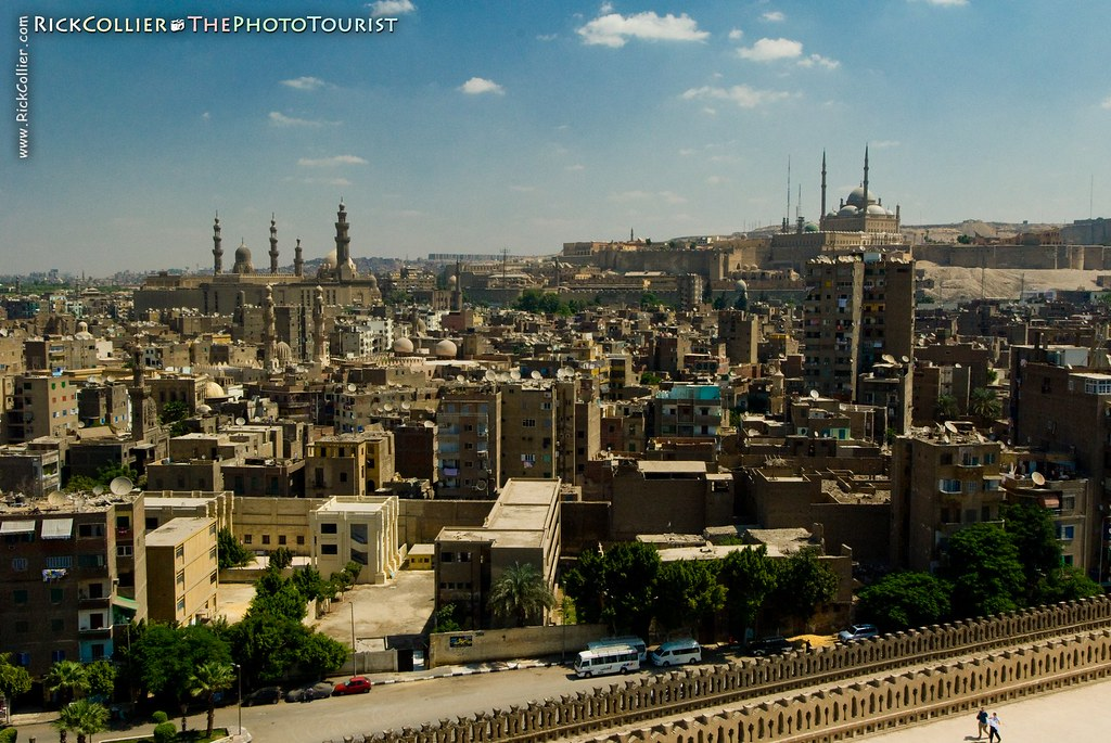 The Cairo city skyline as seen from the top of the spiral minaret at Ibn Tulun mosque, featuring the mosque of Sultan Hassan on the left and Citadel of Saladin on right
