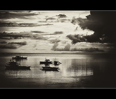moments..that stay with you long after (explored, front page) (PNike (Prashanth Naik..back after ages)) Tags: sea sky bw white reflection water sepia clouds standing boats island blackwhite interestingness still interesting nikon waiting asia philippines explore dreams bohol fishingboats explored d3000 pnike yahoo:yourpictures=blackandwhite