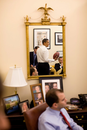 President Barack Obama is reflected in a mirror during an impromptu drop-by visit with speechwriters in David Axelrod's office in the West Wing of the White House on May 21, 2009.