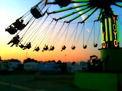 a ride at the state fair with people swinging way out in the air on seats