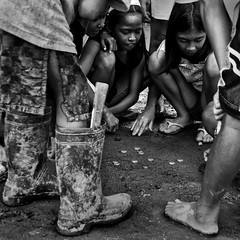 Smoky Mountain, Manila - Children at Play (Mio Cade) Tags: boy food white storm black girl work children coin garbage toddler asia child play feeding boots wind labor ministry philippines social aid disaster rubbish manila labour push feed parma cart laborer crisis typhoon scavenger reportage peso smokymountain labourer tondo ondoy childrenbestphoto