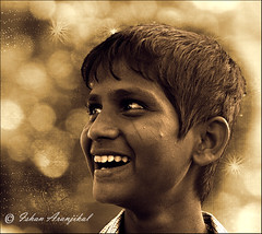 The Merchant of Wishes . . .             [EXPLORED] (Ishan Aranjikal) Tags: street boy portrait bw india beautiful smile smart sepia canon hair kid eyes truth candles child teeth mary joy innocent steps happiness kittens fair mount textures portraiture bombay laugh innocence vendor mumbai bandstand sublime pure pleasant glint bandra mountmary bandrafair interestingness312 interestingness498 interestingness401 bookeh bukeh mywinners 1000d canon1000d ishanaranjikal 20september2009 candlesseller uploadedon20september2009