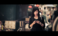 sms (millan p. rible) Tags: street light woman mobile hongkong phone bokeh candid streetphotography naturallight stranger cinematic sms anamorphic cinemascope canonef70200f28lisusm canoneos5dmarkii millanprible