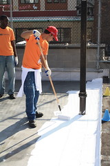 A volunteer paints the LIC YMCA roof after the press conference.
