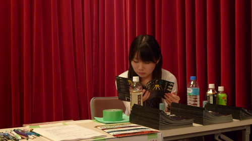 Tsunaoka reading the brochure
