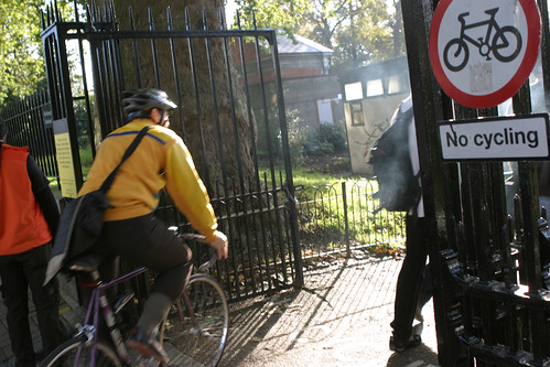 No Cycling sign in London park; cyclist ignoring
