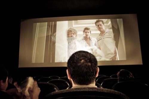una cabeza cubriendo la pantalla de cine