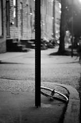(m. wriston) Tags: city light urban blackandwhite bw usa white black bike sign contrast digital america lens 50mm prime evening nikon focus shadows dof bokeh hill spokes maryland tire baltimore september sidewalk manual nikkor 50mmf18d 2009 butchers f18d d40 boyghost michaelwriston