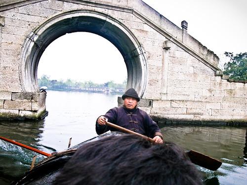 东湖秦桥前划乌篷船的老者