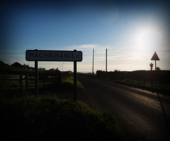 (.CellarDoor Photography.) Tags: road blue sky grass sunshine sign clouds fence photography scotland shadows bluesky olympus powerlines flare machrihanish sunflare greengrass townsign olympuse500 flickrstream gilliansimpson cellardoorphotography flickrphotograph machrihanishsign