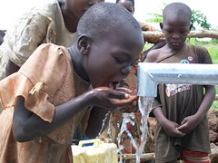 A child enjoys the clean water from the newly finished well